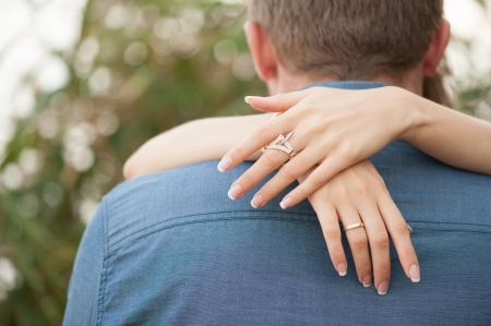 spouses: Woman s hands with the bracelet embracing the man s neck