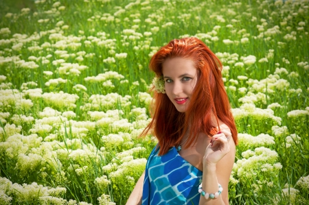 yarrow: Portrait of smiling ginger woman on the blooming meadows Stock Photo