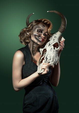 Portrait of a woman with cow s skull in her hands photo