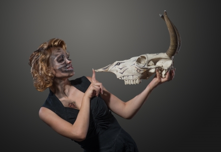 Woman with cow s skull in her hands, face to face photo