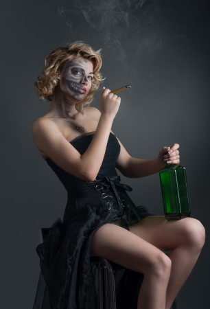 Portrait of drinking and smoking woman with painted skull photo