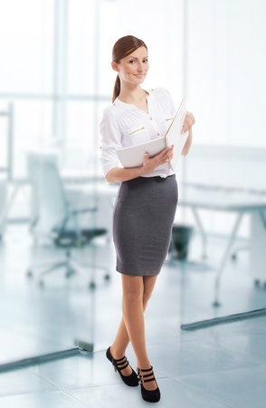 Pretty smiling office lady with open notebook in her hands, office background Stock Photo - 16546537