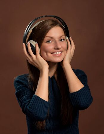 Music lover  Portrait of smiling young woman in headphones, dark brown background photo