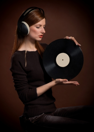 phonograph: Woman in headphones looking at the old gramophone record in her hands, on dark brown background