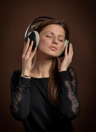 音楽愛好家音楽、暗褐色の背景を楽しんでいるヘッドフォンでの女性の肖像画 写真素材