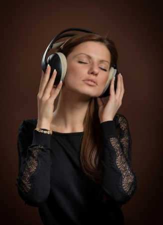 sense: Music lover  Portrait of woman in headphones enjoying the music, dark brown background