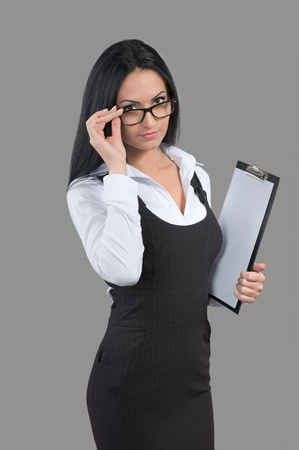 strict: Young woman with papers in her hand looking over glasses Stock Photo