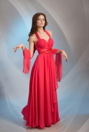 vestido de noche: Joven y bella mujer en vestido de noche rojo, sobre fondo gris