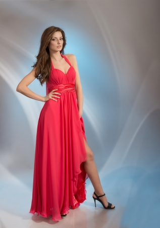 Beautiful young woman in red evening dress looking at camera, on grey background photo
