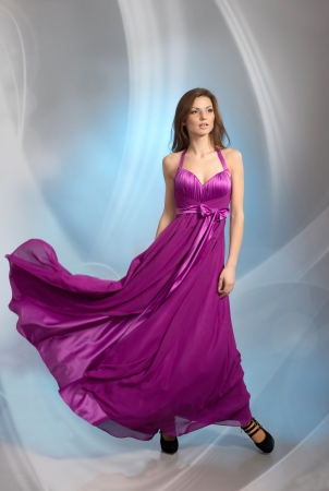 Beautiful young woman in plum violet evening dress, on grey background Stock Photo - 17341290