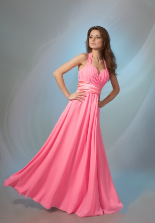 Beautiful young woman in pink evening dress, on grey background Stock Photo - 17341273