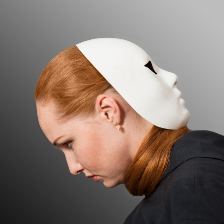 Two faces  Red-headed woman with white mask worn on the back of her head photo
