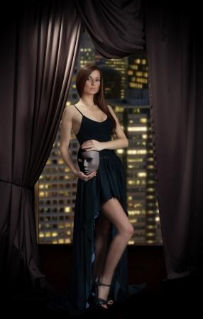 窓の近くに立っている彼女の手でマスクとイブニング ドレスの魅惑的な女性 写真素材 - 17477864
