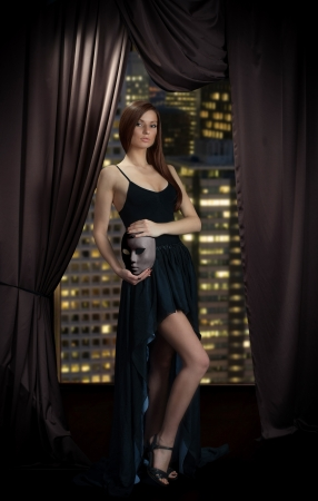 Seductive lady in evening dress with mask in her hands standing near the window