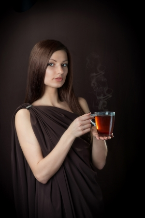 agreeable: Friendly young woman with the cup of tea in her hands, dark brown background Stock Photo