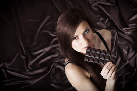 Portrait of pretty young woman nibbling the bar of chocolate, view from above