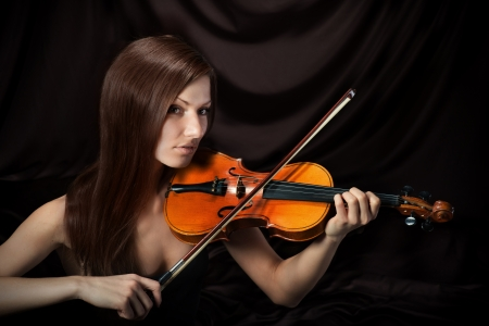 women subtle: Romantic portrait of beautiful woman with violin, dark background