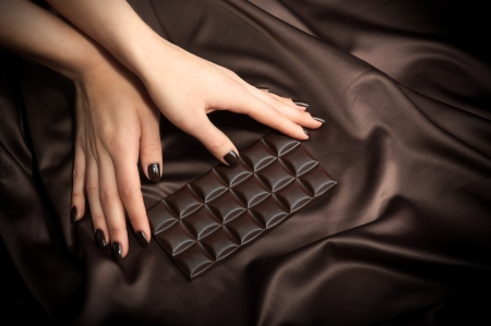 nail varnish: Closeup of female hands touching the dark chocolate bar  Stock Photo