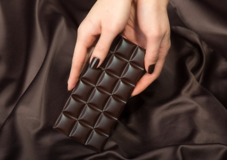 Female hands holding the dark chocolate bar