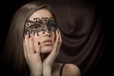 暗い茶色の背景にレースの黒いマスクで美しい女性のクローズ アップの肖像画 写真素材