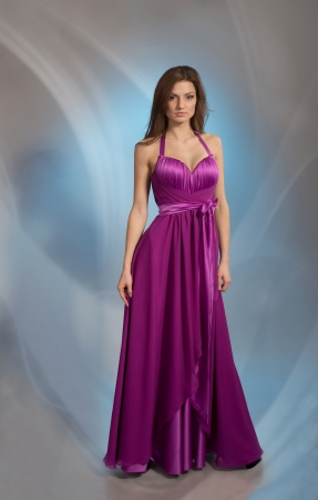 Beautiful woman posing in plum violet evening dress, on grey background Stock Photo - 17935021
