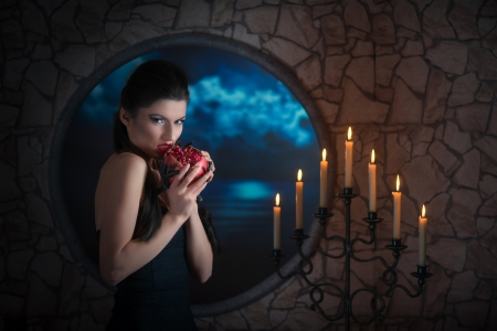 Fantasy style portrait of demonic woman biting a pomegranate photo