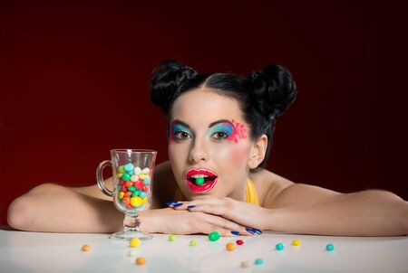 dragee: Portrait of funny woman with colorful makeup and candy drops