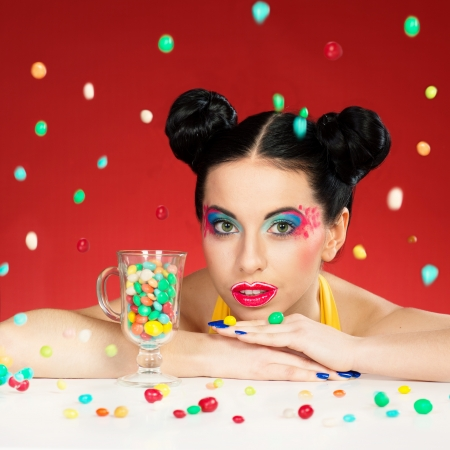 dragee: Portrait of funny woman with colorful makeup under the falling candy drops