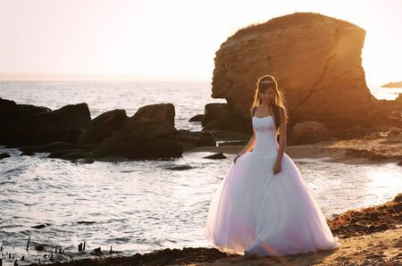 Beautiful bride walking along the seaside at sunset photo