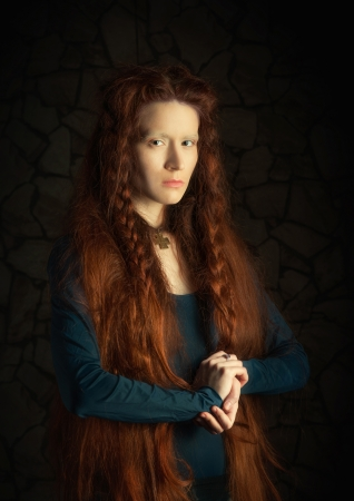 Portrait of young woman with long red hair  Image stylized as old picture photo
