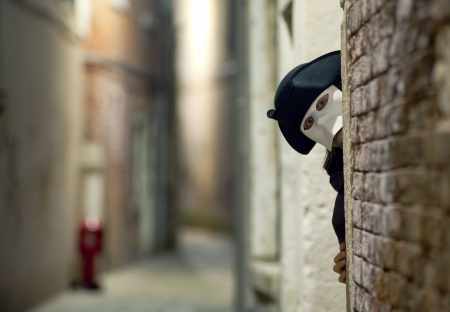 Man in mask looking around the corner, on Venice street photo