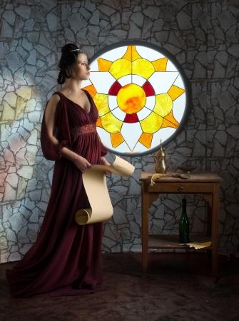 彼女の手でスクロールと赤いドレスを着た女性の中世スタイルの肖像画 写真素材