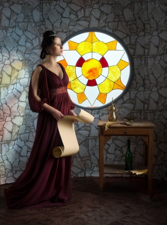 Medieval style portrait of woman in red dress with the scroll in her hands Stock Photo