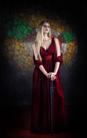 middeleeuwse jurk: Portret van de vrouw in middeleeuwse kleding met het zwaard