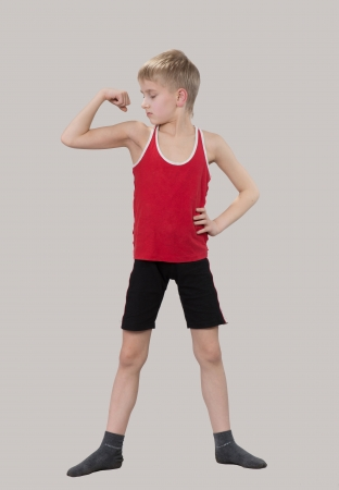 Boy looking at his muscles photo