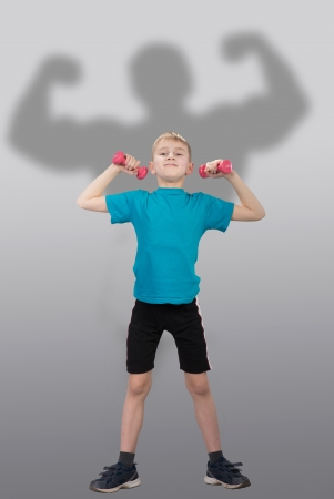 Smiling boy with children s dumbbells on gray background photo