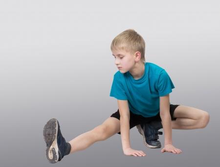 children s: Sportive boy stretching his leg, gray background Stock Photo