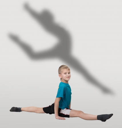 Smiling boy doing horizontal splits with dancer s silhouette behind him