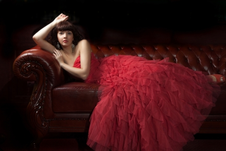 Woman in red evening dress lying on the sofa, dark background  photo