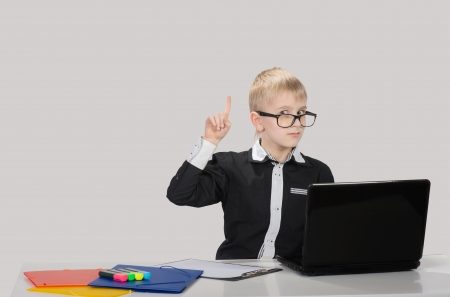 Funny smart boy with laptop raising the index finger up and looking at camera photo