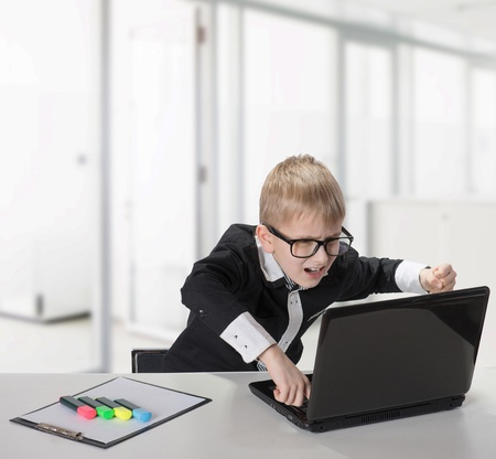 Angry schoolboy with laptop, indoors portrait photo
