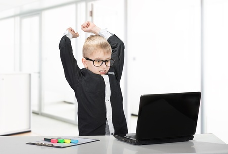 Angry schoolboy raises his fists threateningly at laptop, indoors portrait photo