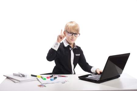 Smart boy with laptop raising the index finger up, on white background photo