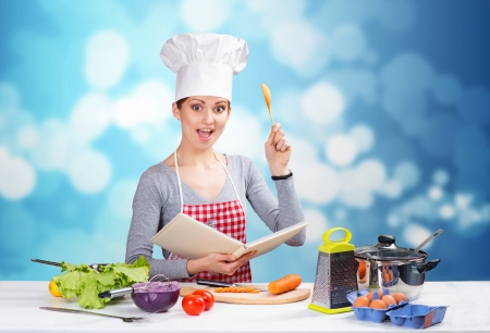 Woman in chef s hat reading cookbook and raising up a spoon, with blue boke background