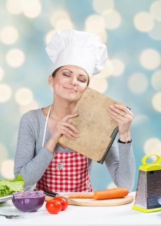 delantal: Retrato de mujer con sombrero de cocinero s sonriente con libro de cocina de la abuela s en el fondo azul abstracto Foto de archivo
