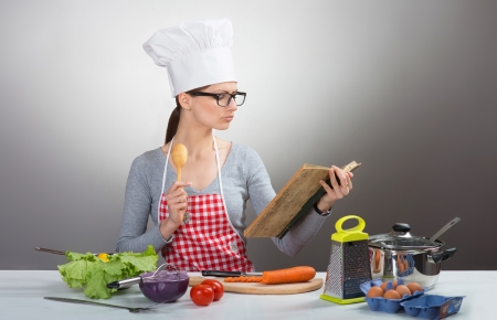 Pretty serious woman cooking with old cookbook, on gray background photo