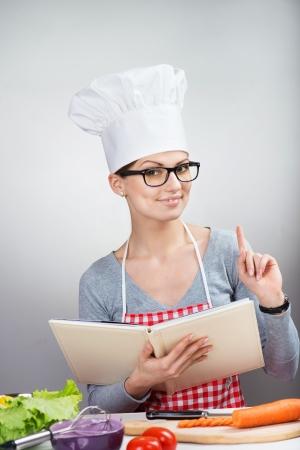 delantal: Retrato de mujer con sombrero de cocinero s sonriente con el libro de cocina levantando el dedo índice hacia arriba, fondo gris Foto de archivo