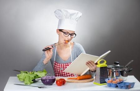 灰色の背景上の料理と料理のきれいな女性