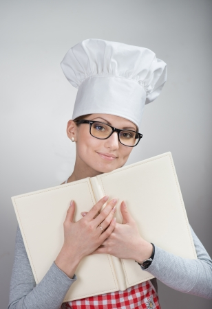 Closeup portrait of smiling woman in chef s hat with the book on grey background photo
