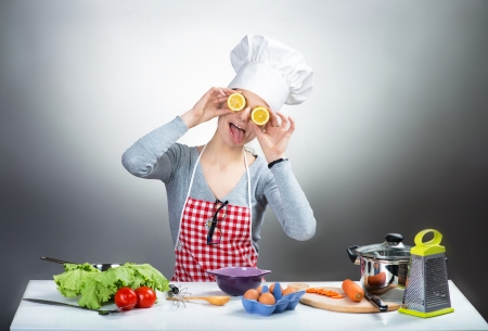 Crazy cooking woman with lemon eyes on grey background